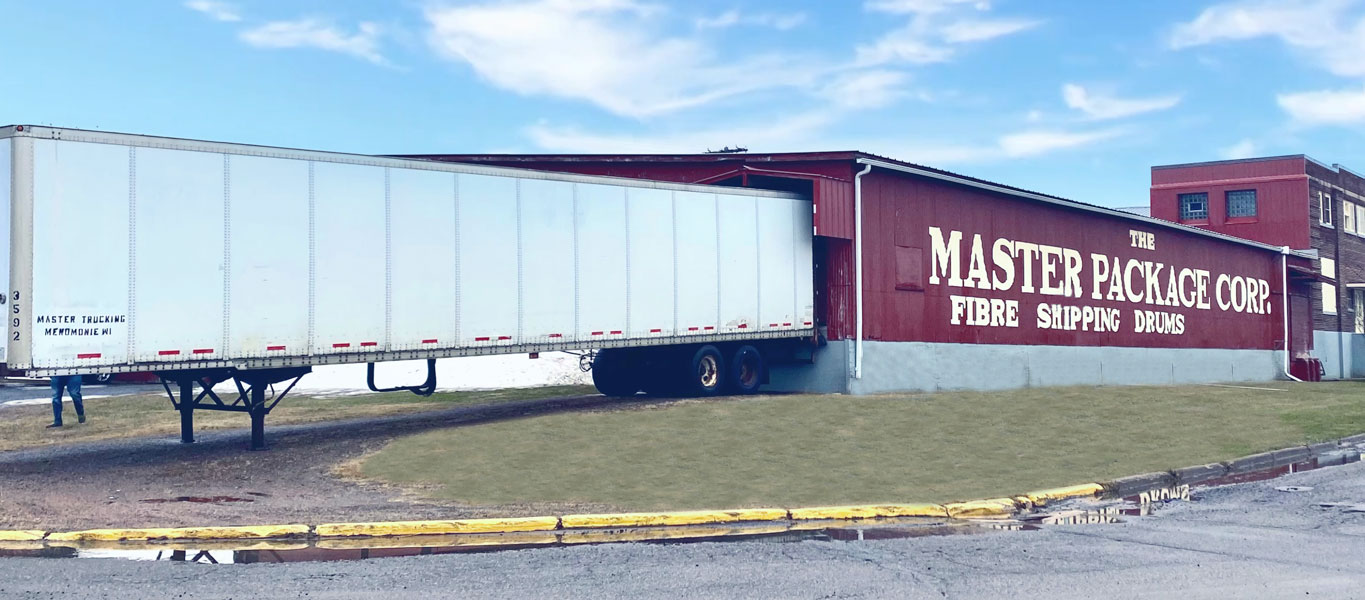 The Master Package facility with truck loading barrels The Master Package Fibre Shipping Containers