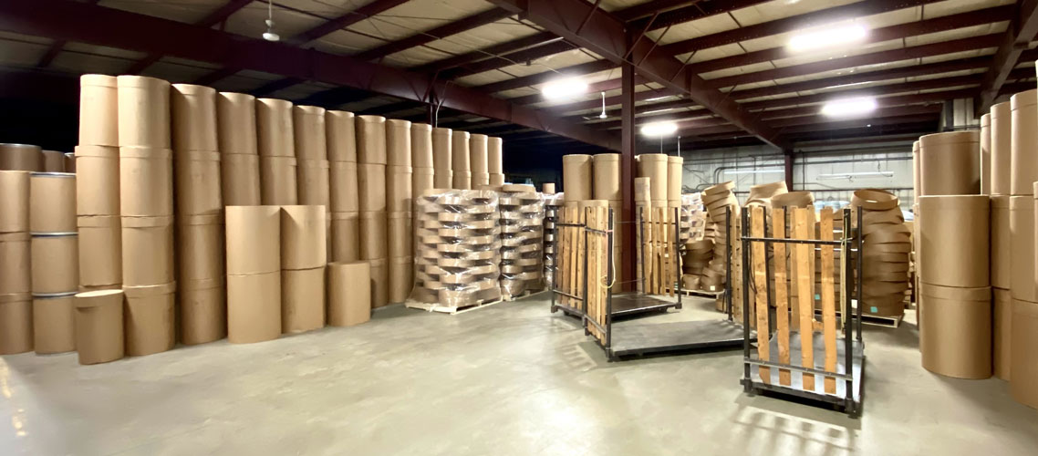 corner view of warehouse with fibre barrels and pallets ready to ship The Master Package Fibre Shipping Containers