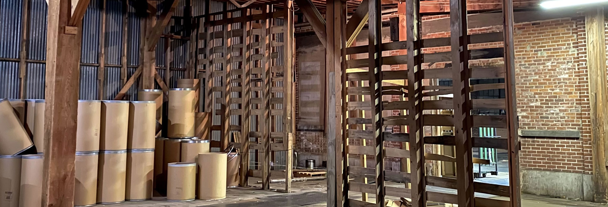 barn-like warehouse with empty shipping barrels at The Master Package Fibre Shipping Containers